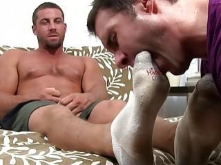 Muscular gay hunk has his socks and bare feet worshiped