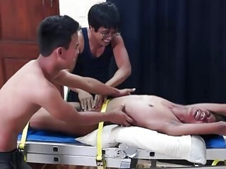 Asian slut is tied down to be tickled by a group of cruel lovers