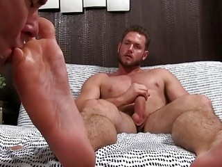 Buff fucker jerks while his feet are sucked