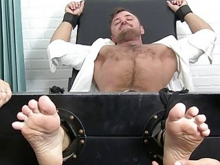 Dashing stud restrained by two gays for kinky erotic tickling