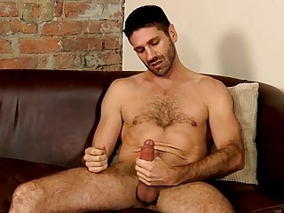 Hairy hunk strips naked and tugs on his big cock