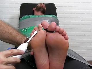 Bearded stud restrained to have his bare feet playfully tickled
