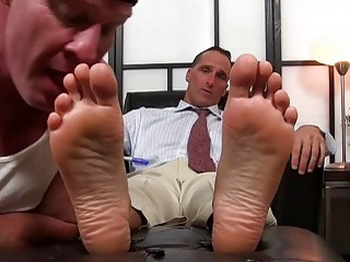 Gay businessman with a foot fetish has his toes sucked