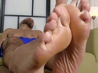 Handsome gay hunk takes socks off to massage his feet
