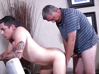 Grandpa bangs his young and tattooed grandson on the kitchen chair