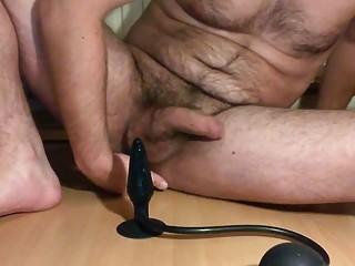 Using a butt plug while masturbating his sausage