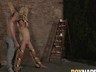 Skinny submissive gay tied up for BDSM wax torturing by dom